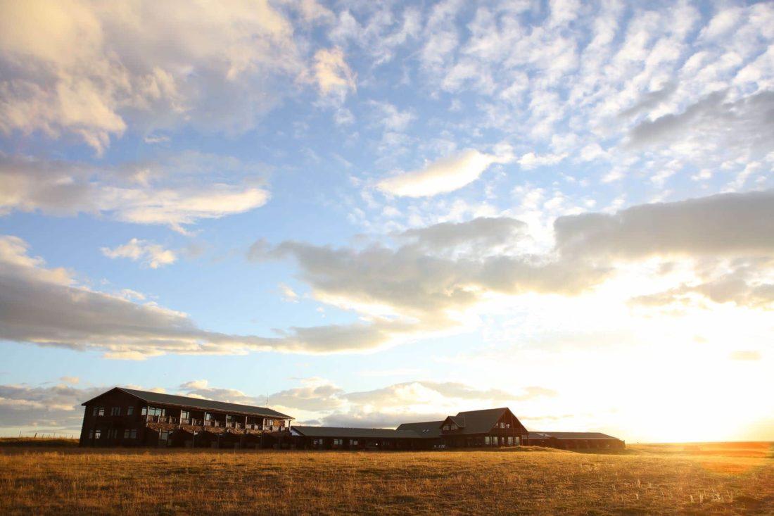 Blauwe-hemel-met-wolken-veld-en-gebouw